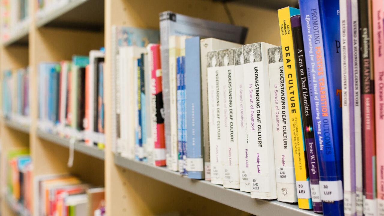 Lähikuva kirjahyllystä, jossa kuurojen yhteisöön liittyvää kirjallisuutta.