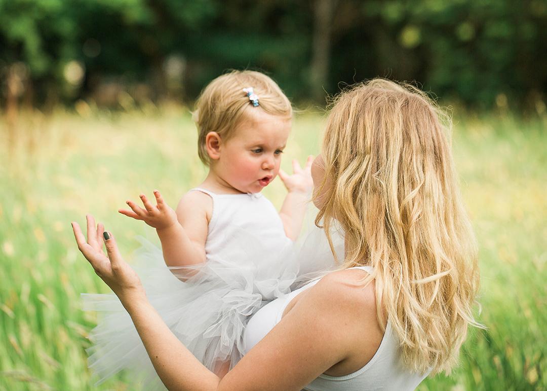 Noin 2-vuotias lapsi viittoo äidin sylissä.