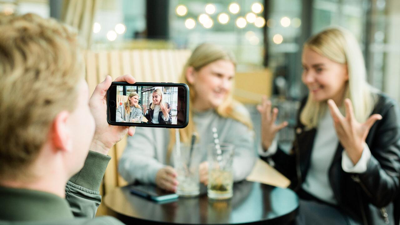 Nuori mies kuvaa kahvilassa, kun kaksi nuorta naista viittovat videoviestiä.