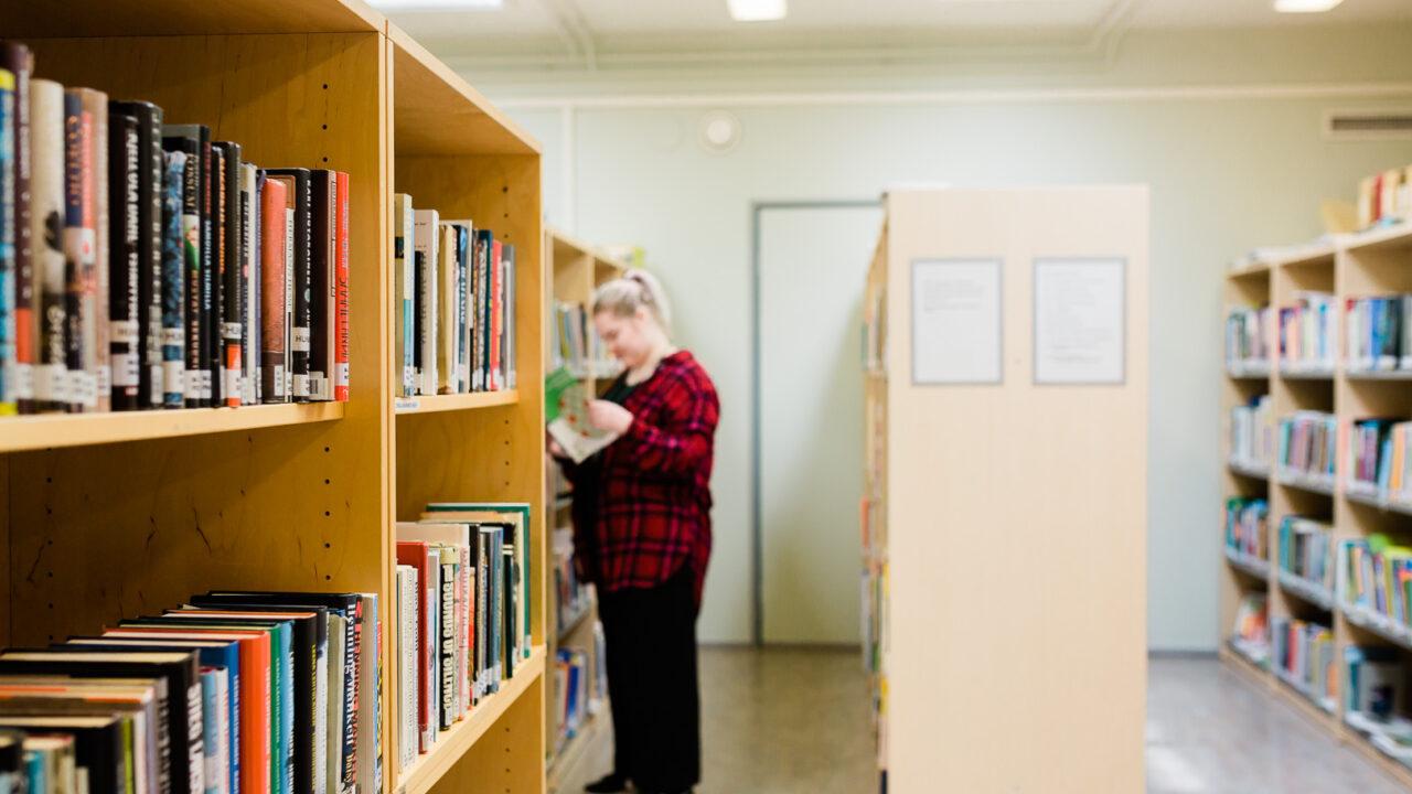 Kirjahyllyrivejä kirjastossa. Taaempana seisoo tyttö hyllyä tutkailemassa.