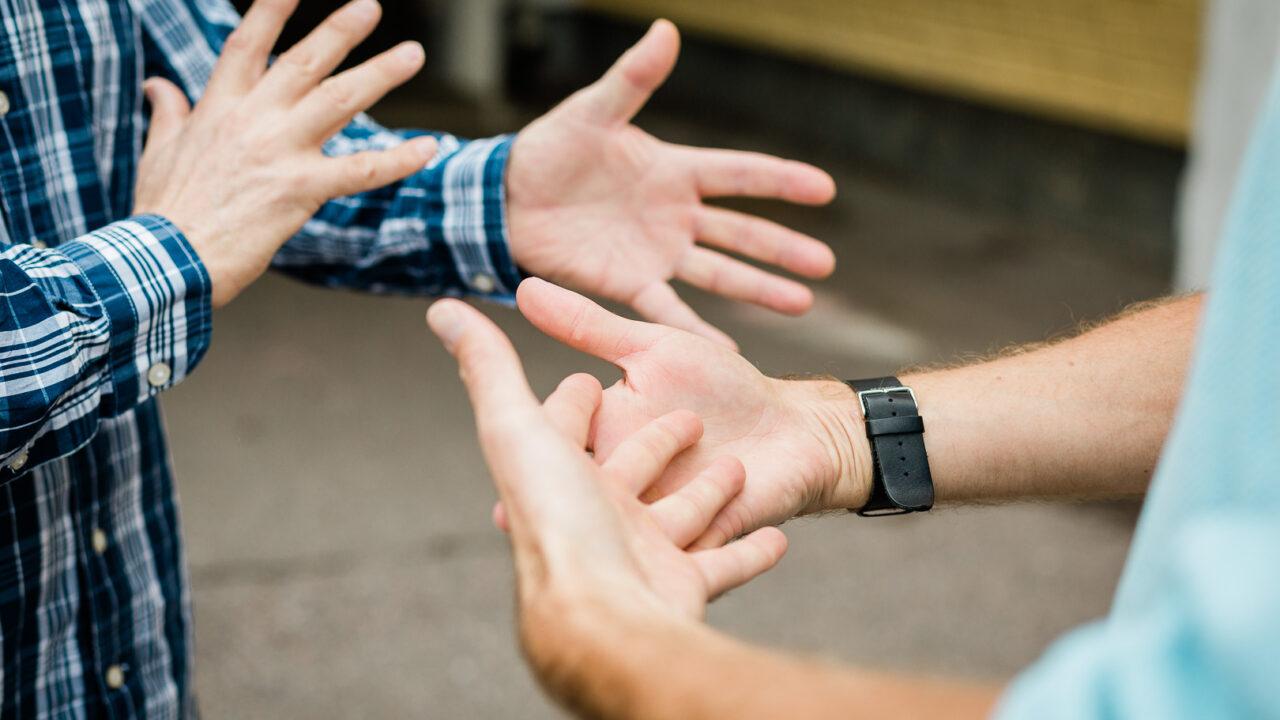 Kuvassa vain kahden henkilön kädet, jotka muodostavat yhdessä viittoman: