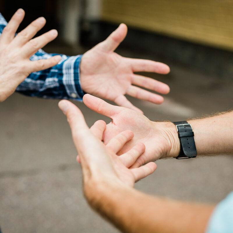 """Kuvassa vain kahden henkilön kädet, jotka muodostavat yhdessä viittoman: """"viittomakieli""""."""