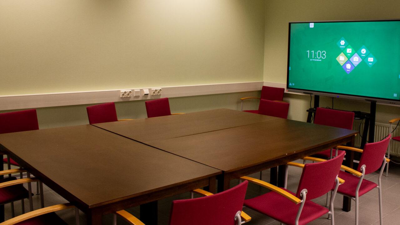 Huone, jossa vaaleat seinät. Keskellä on neliskulmainen pöytä, jonka ympärillä on tuoleja. Seinällä on iso televisio.