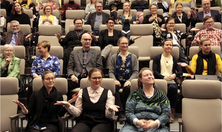 Yleisö istumassa auditoriossa