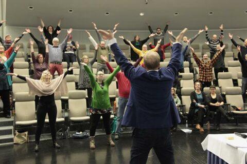 Auditoriossa yleisö jumppaa kädet ylhäällä