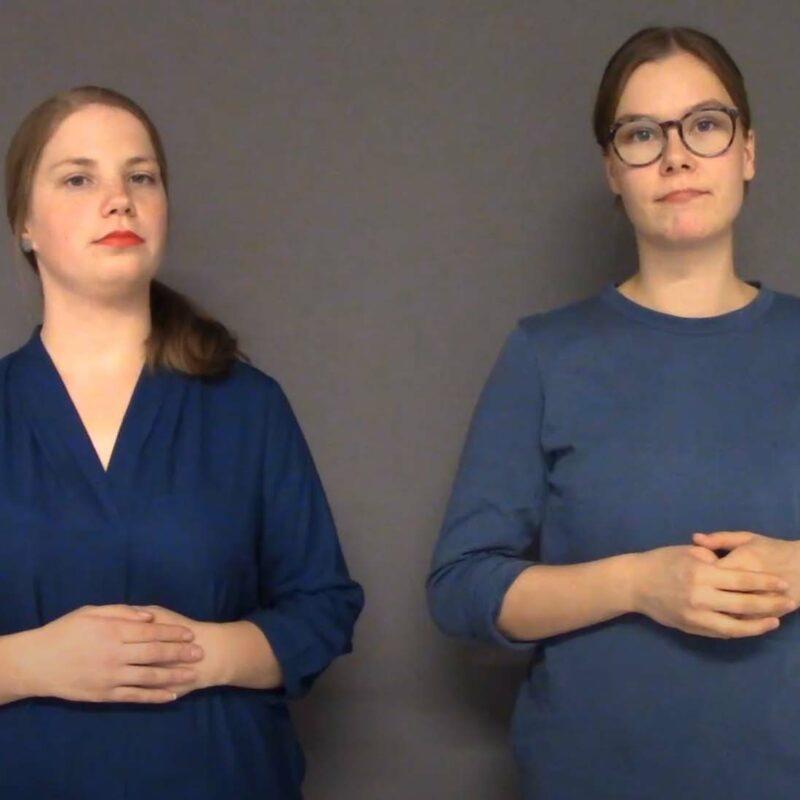 Kaksi sinipaitaista nuorta naista seisoo vierekkäin.