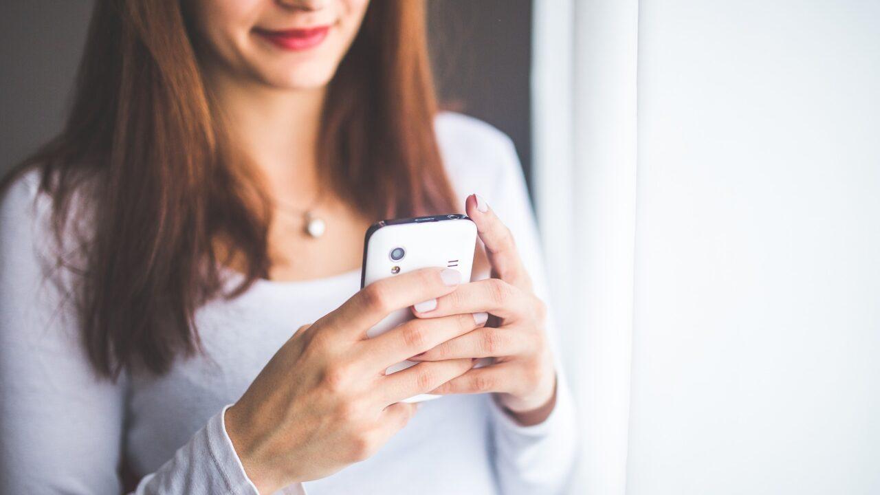Nainen pitelee älypuhelinta käsissään.