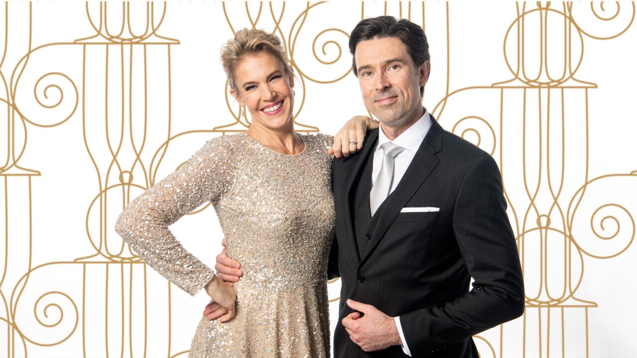 Nainen ja mies hymyilevät juhlavaatteissa.