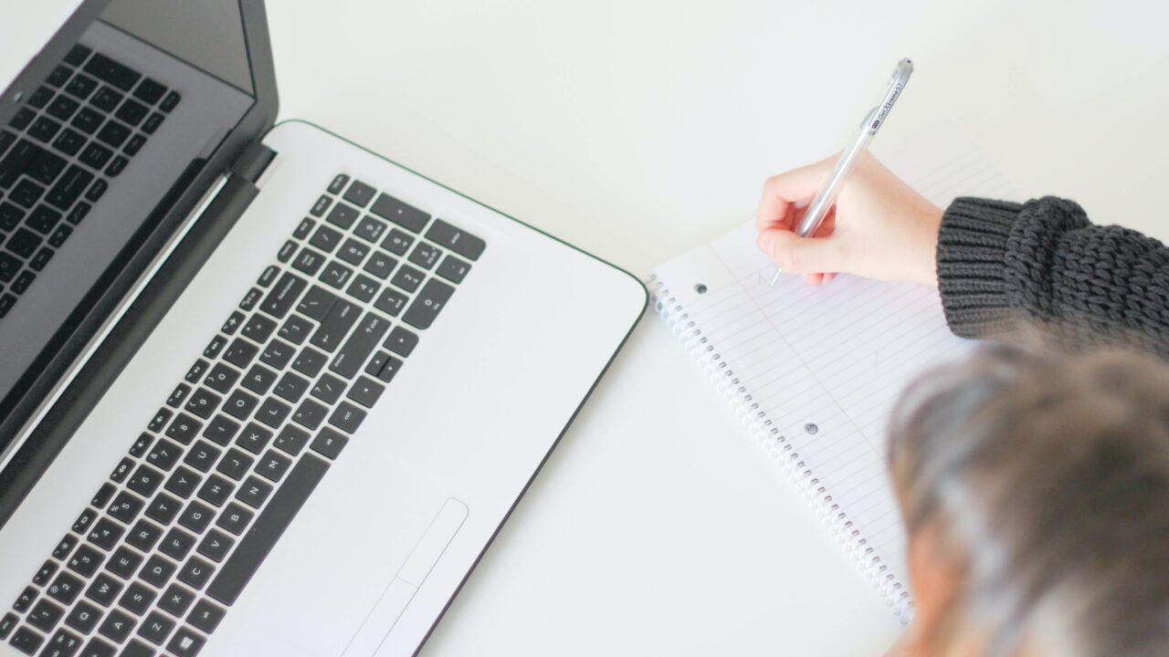 Kannettava tietokone, jonka vieressä henkilö kirjoittaa muistiinpanoja.