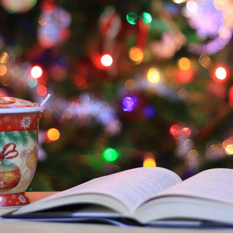 Pöydällä kaakaomuki ja avoin kirja. Taustalla tunnelmallinen joulukuusi valoineen.