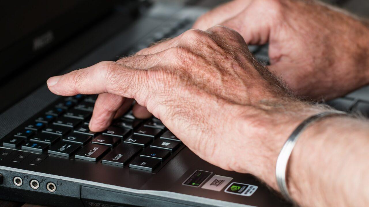 Lähikuva miehen käsistä kirjoittamassa kannettavan tietokoneen näppäimistöllä.