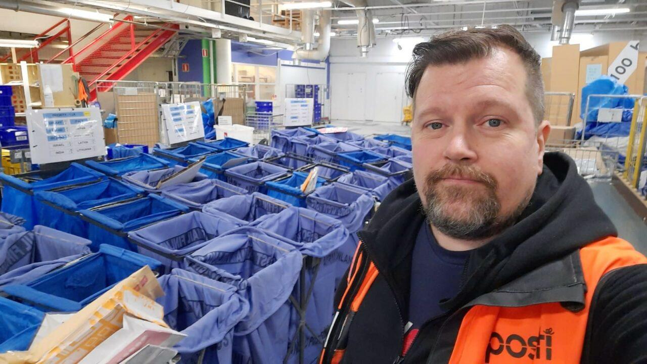 Mies katsoo kameraan postin lajitteluhuoneessa. Taustalla näkyy monta sinistä lajittelusäkkiä.