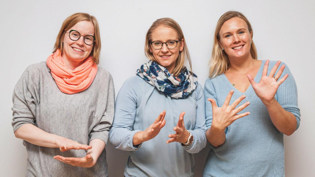 VIKKE-hankkeen kolme työntekijää seisovat vierekkäin ja muodostavat käsillään viittoman: VIKKE.