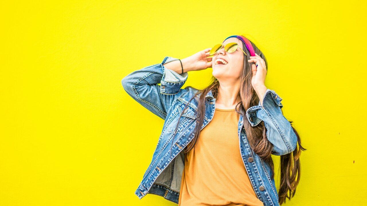 Naurava tyttö katsoo taivaalle aurinkolasit päässä. Tausta on kirkkaan keltainen.