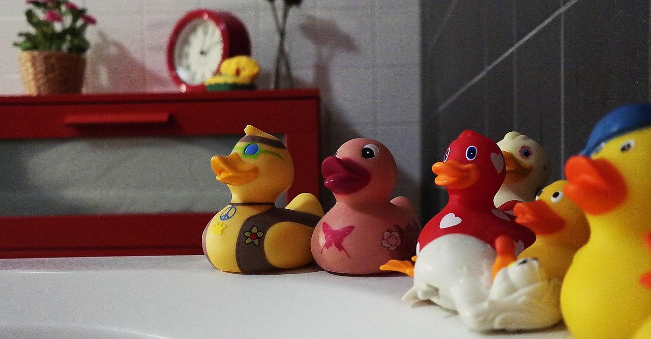Erilaisia kylpyankkoja kylpyammeen reunalla.