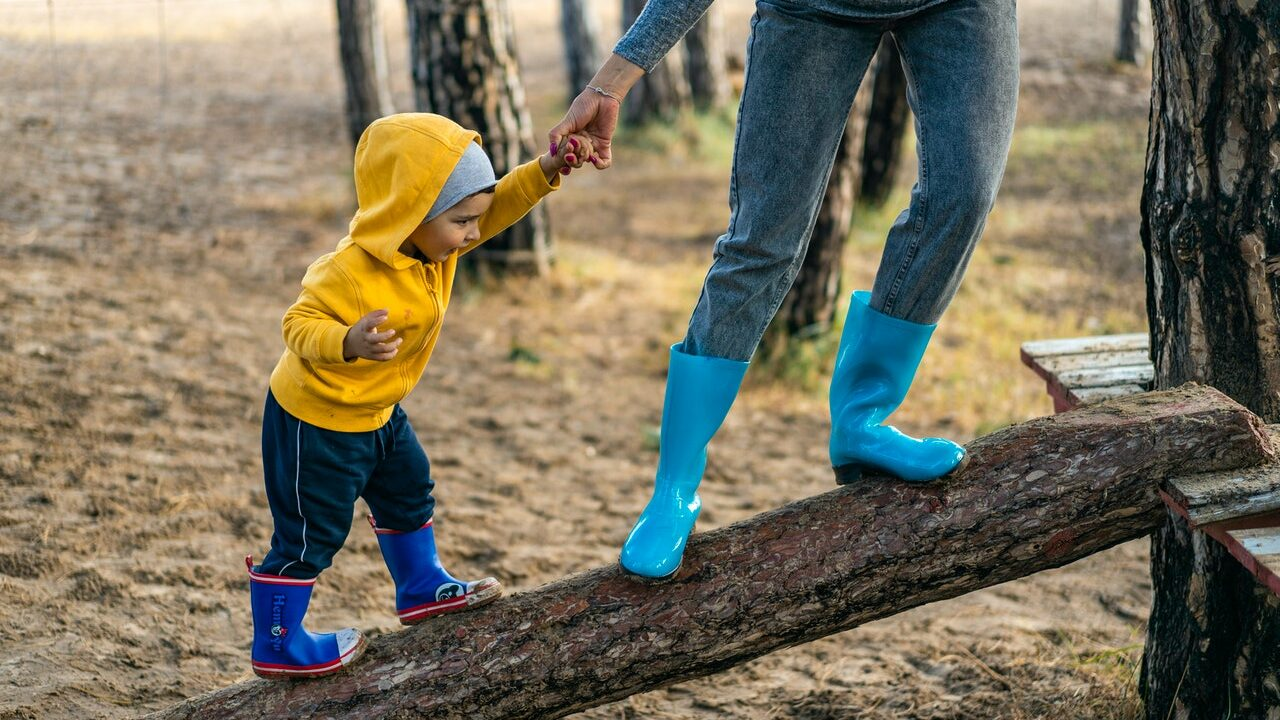 Taapero tasapainoilee tukin päällä äidin tukemana.