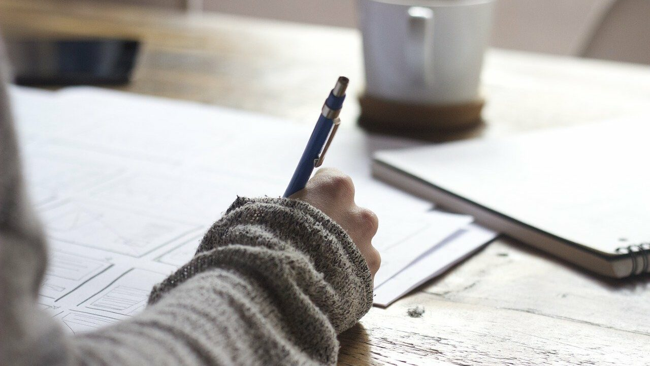 Käsi kirjoittaa muistiinpanoja.
