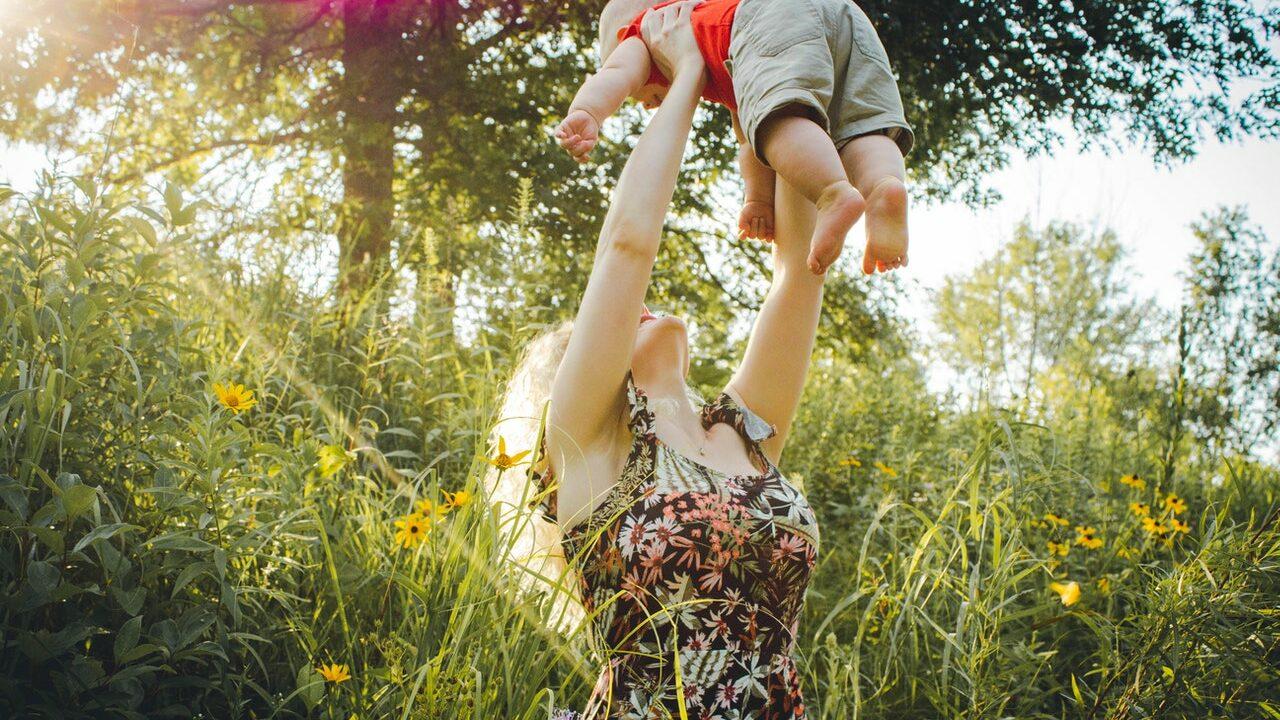 Äiti nostaa vauvaa ilmaan niityllä.