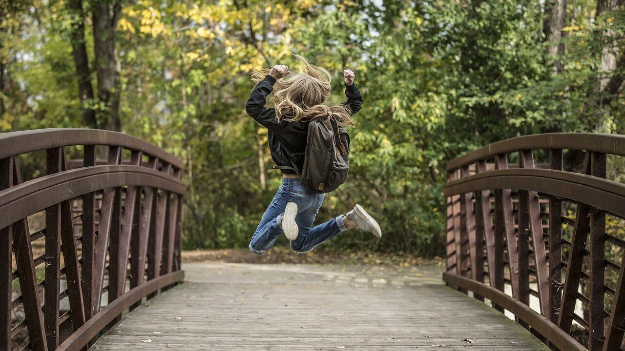 Reppuselkäinen lapsi hyppää ilmaan.