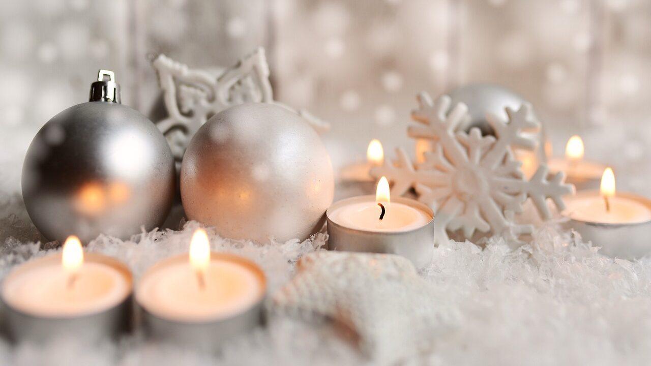 Lähikuva, jossa joulupalloja, lumihiutale-ornamentti sekä tuikkuja.
