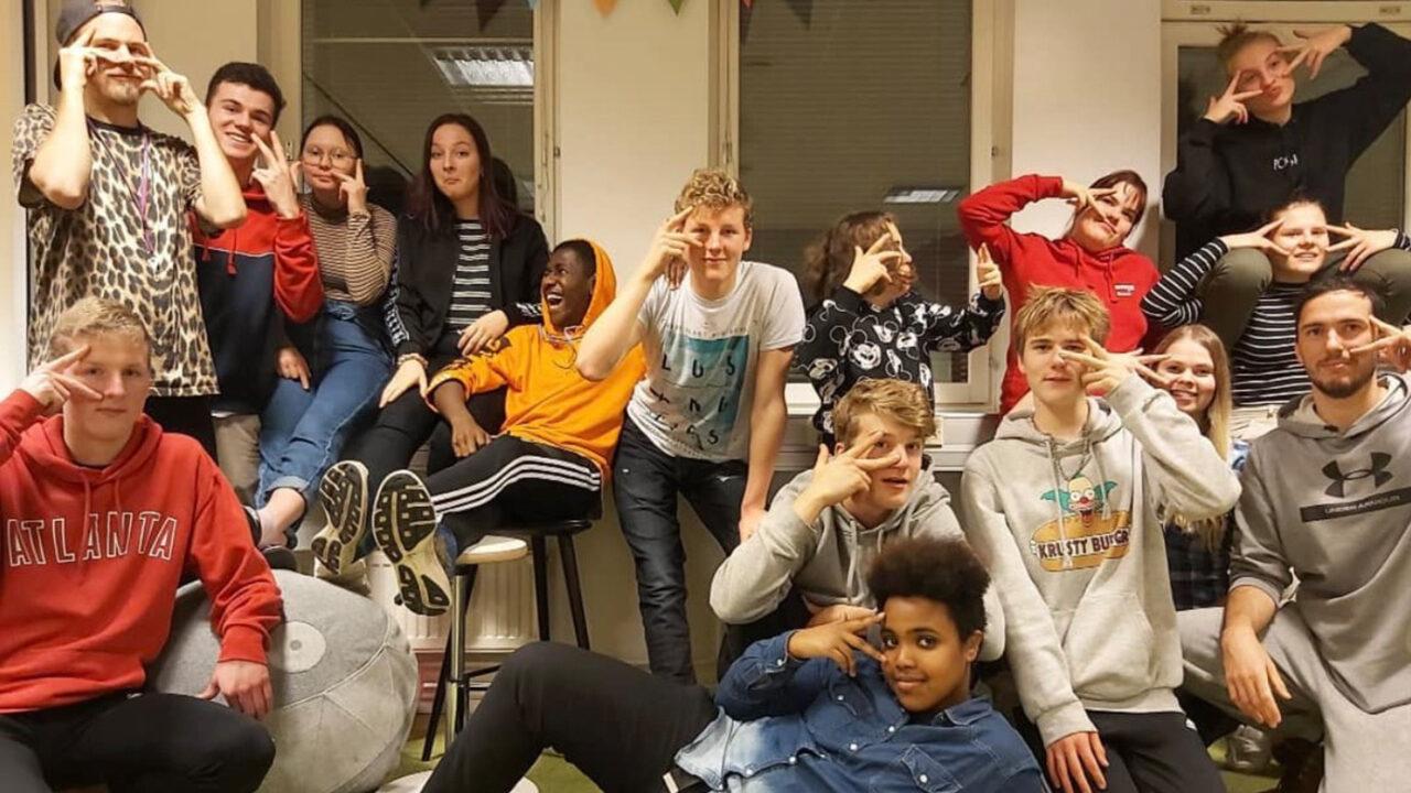 Iloisia nuoria ryhmäkuvassa viittomassa