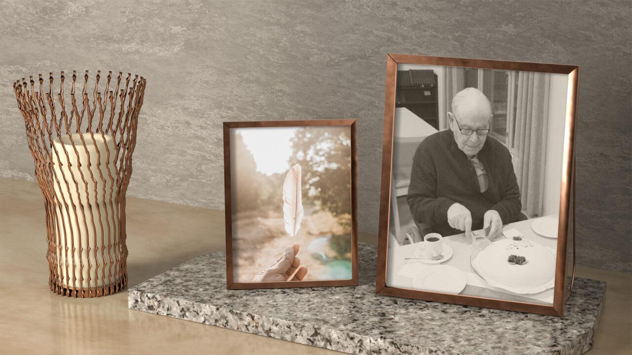 Kynttilä ja kaksi kuvakehystä, joista toisessa höyhen ja toisessa silmälasipäinen mies, joka leikkaa 90-vuotissyntymäpäiväkakkua.