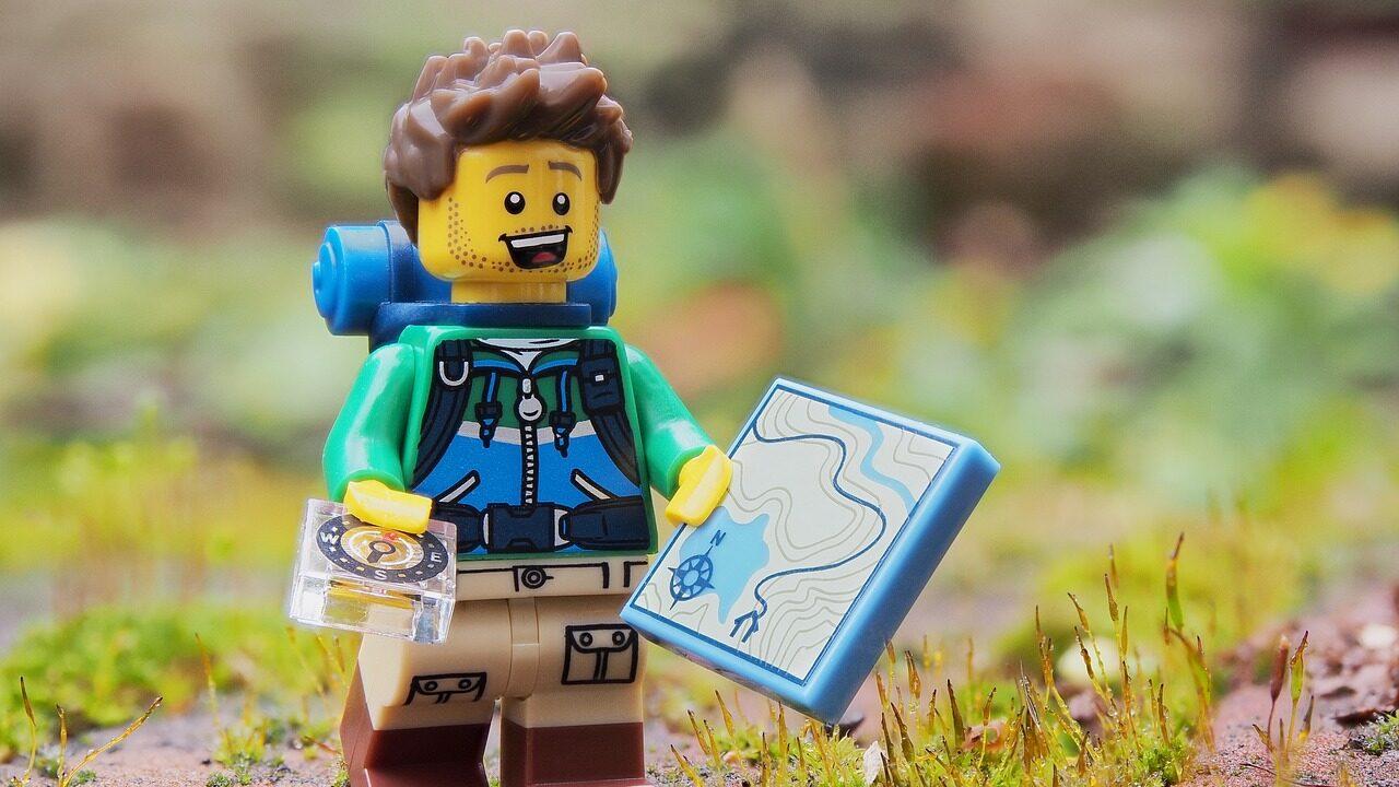 Lähikuva iloisesta reppuselkäisestä lego-ukkelista, jolla on kädessä kartta ja kompassi.