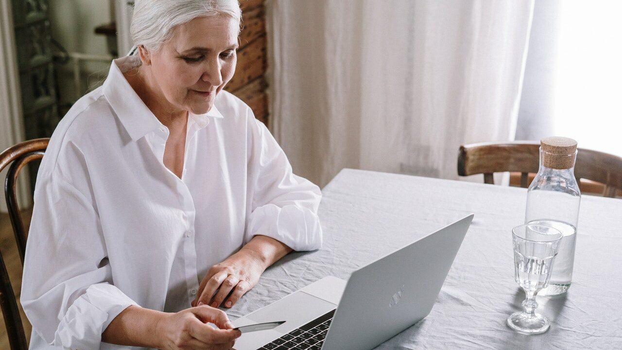 Ikääntynyt nainen puuhailee kannettavalla tietokoneella.