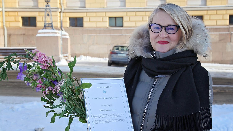 Heta-Leena Sierilä seisoo senaatintorilla ja pitelee käsissään kunniakirjaa ja kukkakimppua.