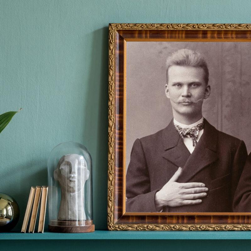 Vintage-kehyksissä Albert Tallrothin kuva. Tallroth katsoo suoraan kameraan käsi rinnan päällä.