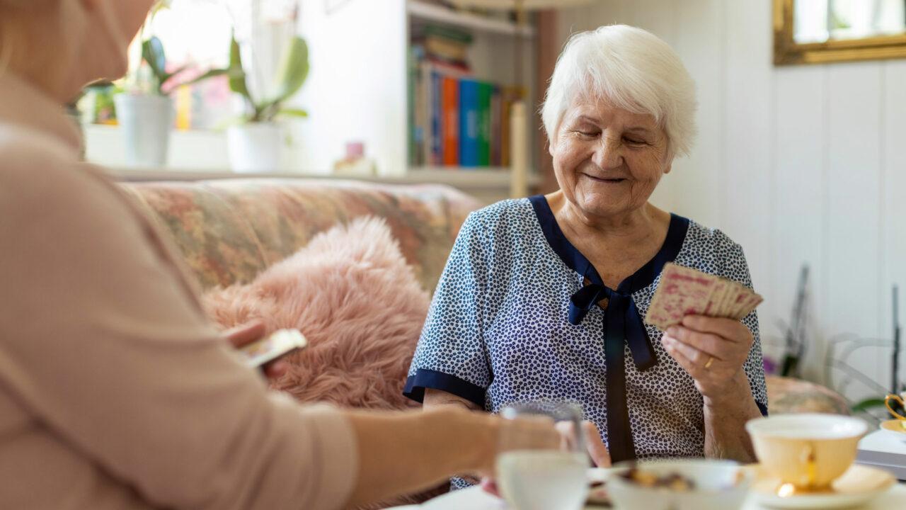 Seniori-ikäinen nainen pelaa korttia tukihenkilön kanssa kotonaan.