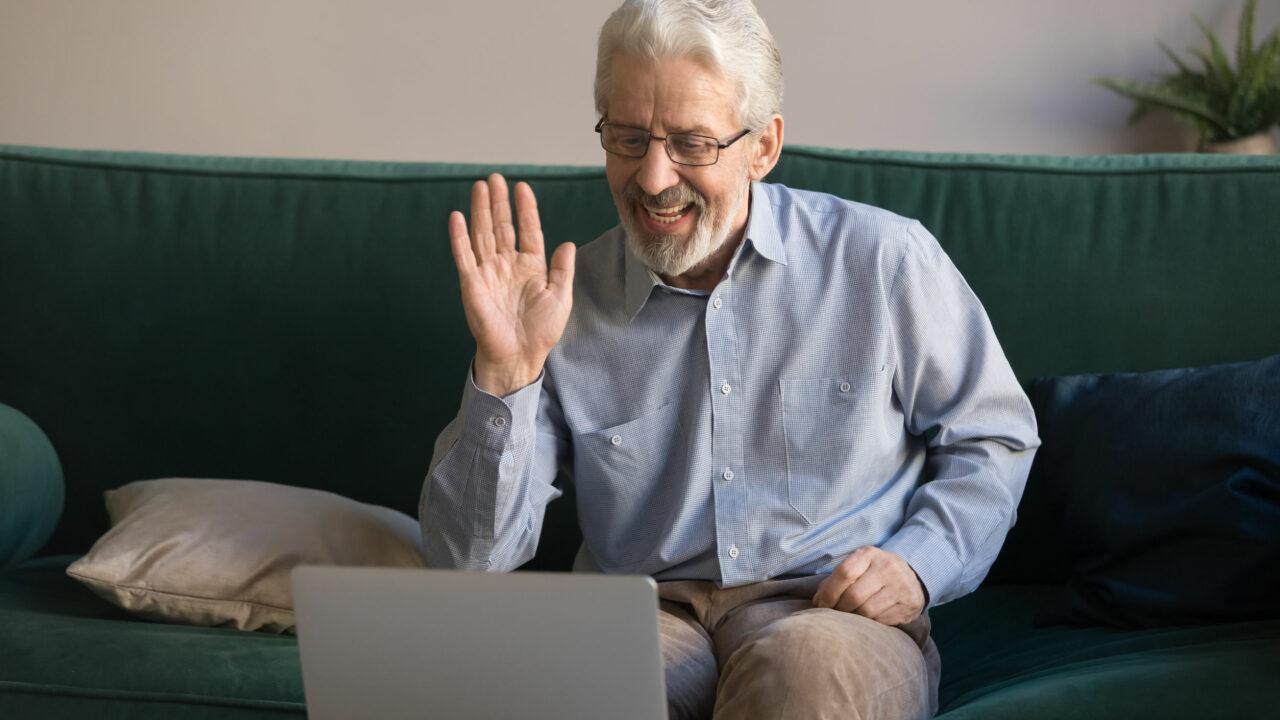 Vanhempi harmaahiuksinen mies katsoo kannettavaan tietokoneeseen ja tervehtii iloisesti.