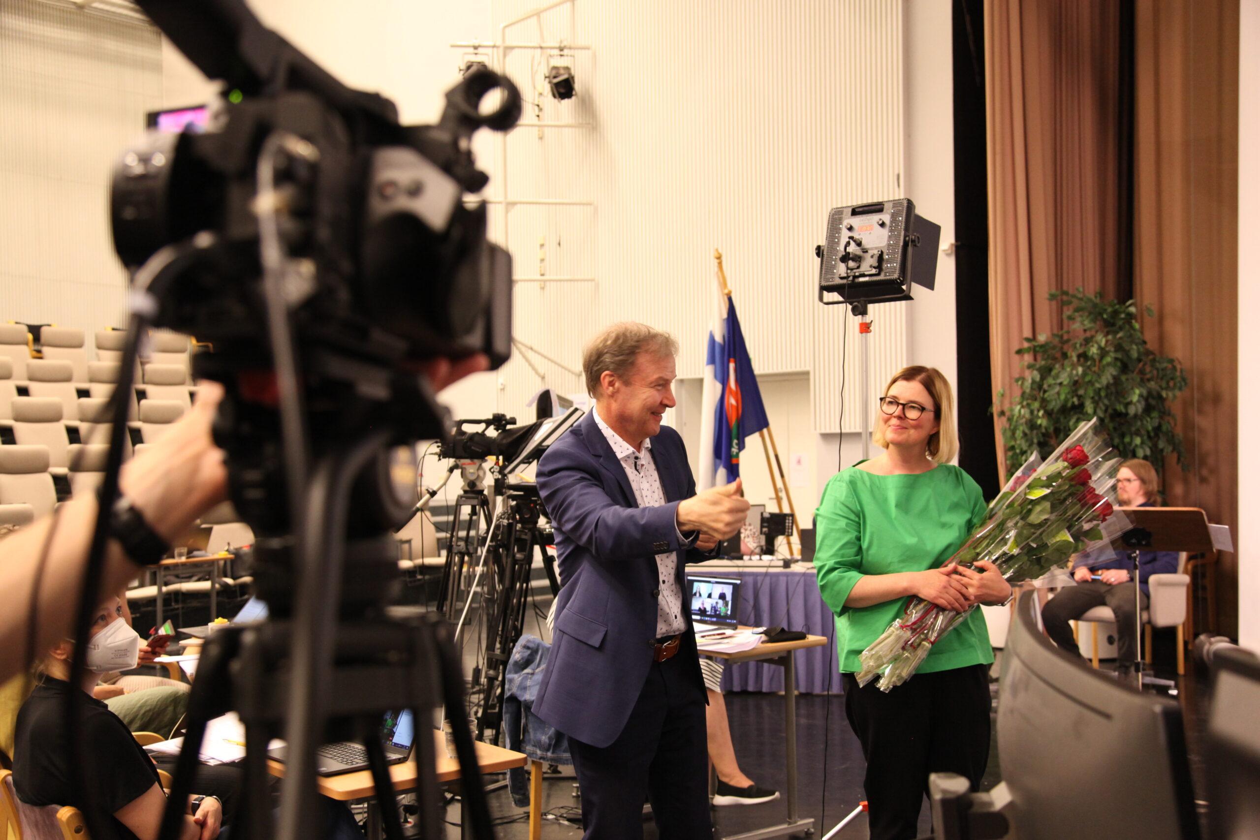 Markku Jokinen viittoo kiitoksia ja Kaisa Alanne pitää kädessää ruusunippua. Kuvan vasemmassa reunassa on kamera.