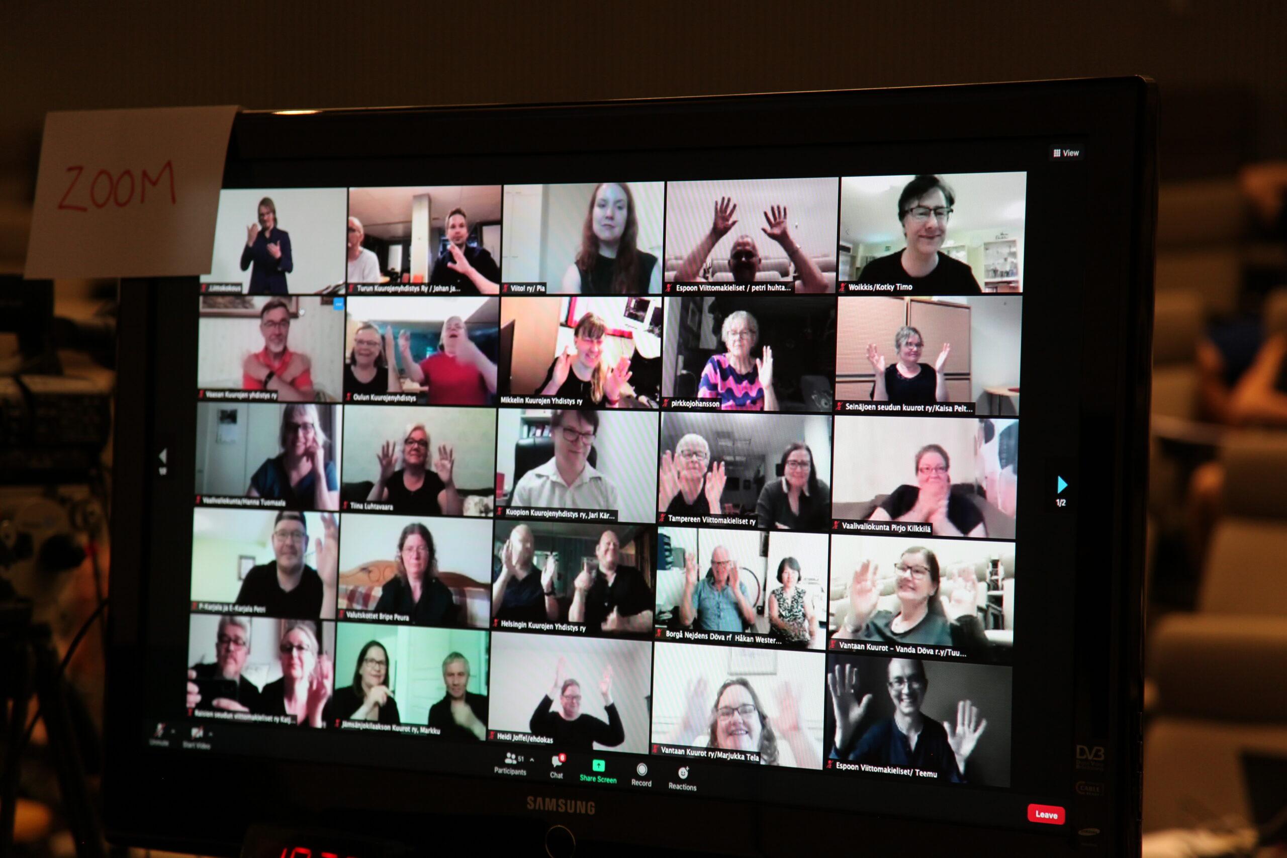 Kuva Zoom-kokouksesta, jossa näytön ruuduissa näkyy edustajia vilkuttamassa.