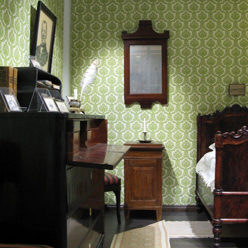 Malmin huone, jossa huonekaluja; sänky, peili, yöpöytä ja lipasto.