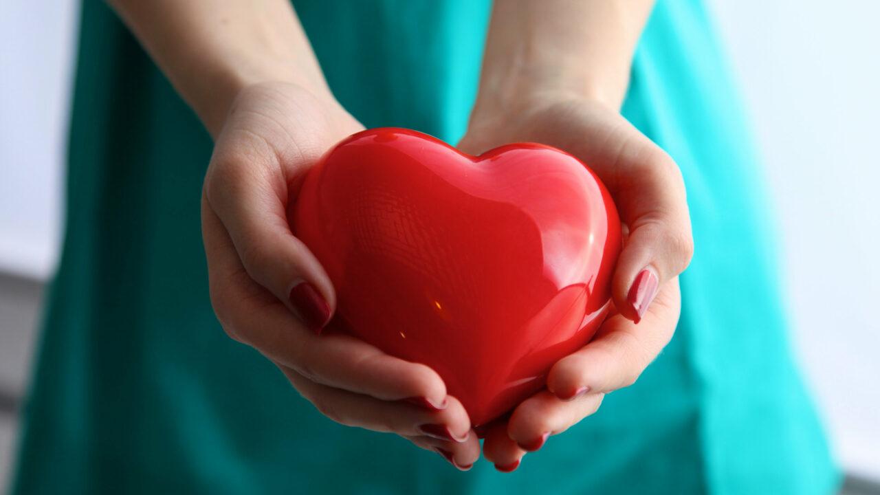 Lähikuva punaisesta sydämestä, jota naisen kädet pitelevät.