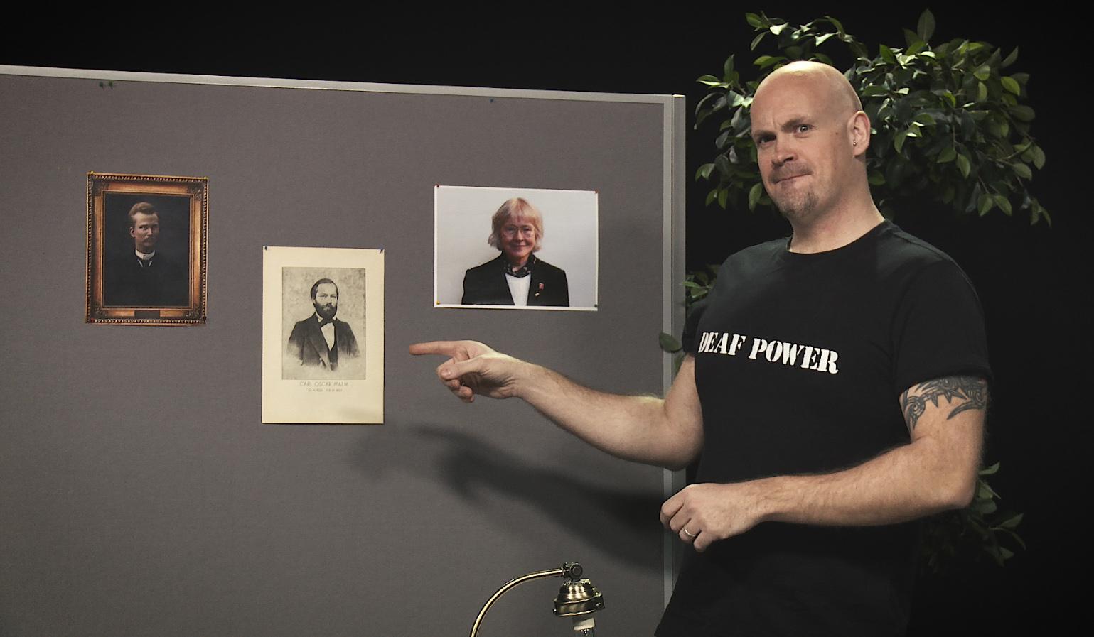 Esiintyjä osoittaa sormella Carl Oscar Malmin kuvaa