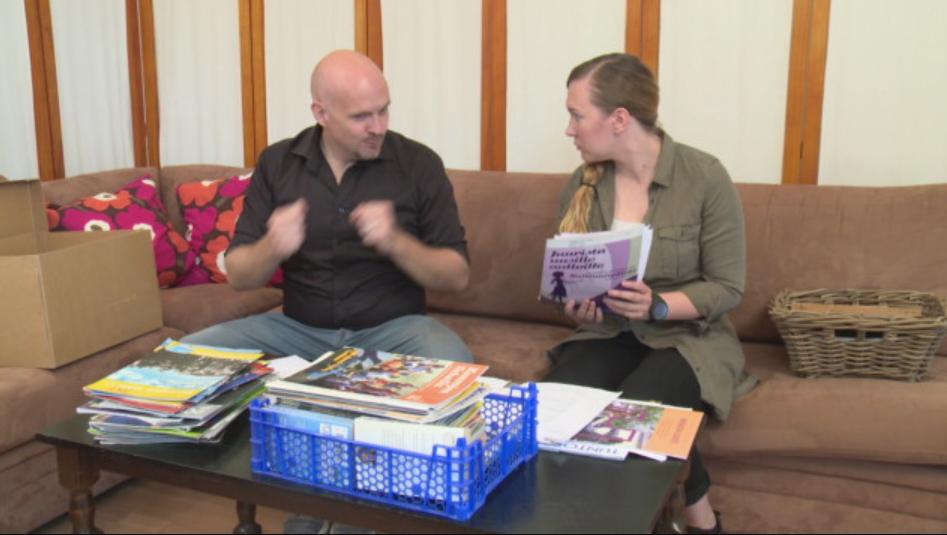 Esiintyjä istuvat sohvalla keskustelemassa, toinen näyttää lehtiä