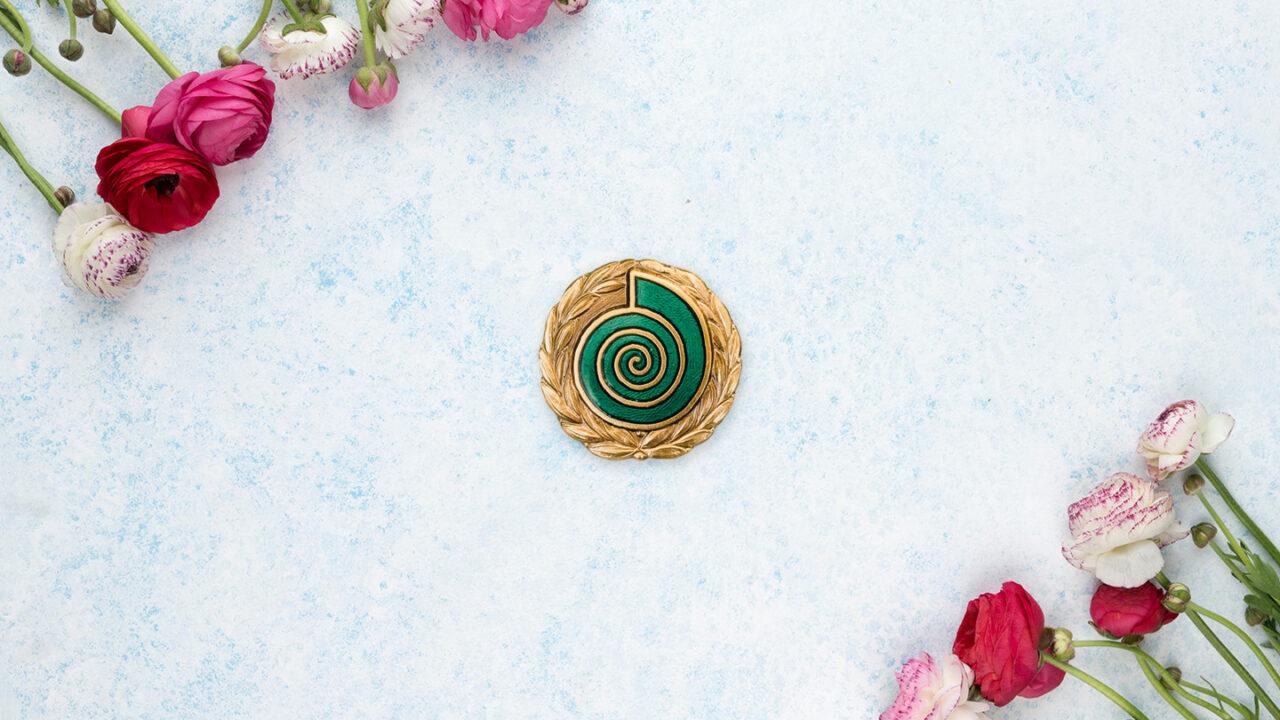 Kuva mitalista kukkien ympäröimänä